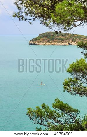 Summertime.Gargano coast: Baia di Campi beach,Vieste-(Apulia) ITALY-Baia Campi  is a picturesque bay framed by olive trees and pinewoods:the bather who practices standuppaddling and in the background the island Campi.