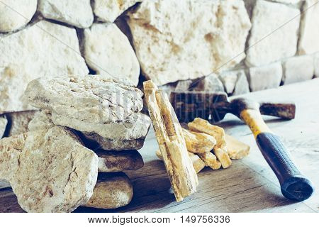 Stack Flagstone And Construction Hammer Against The Wall Of Stone Closeup. Concept Building Repair