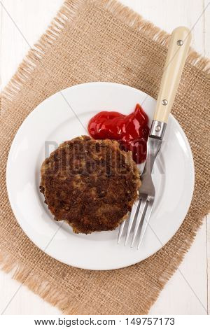 home made fried rissole on a plate with ketchup and fork