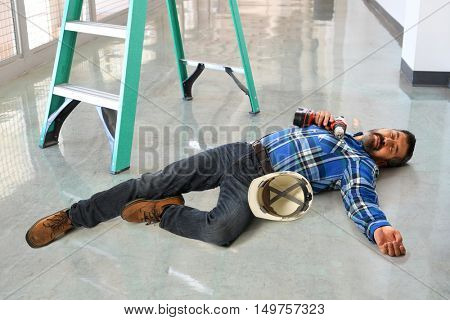 Hispanic worker laying injured on floor next to ladder
