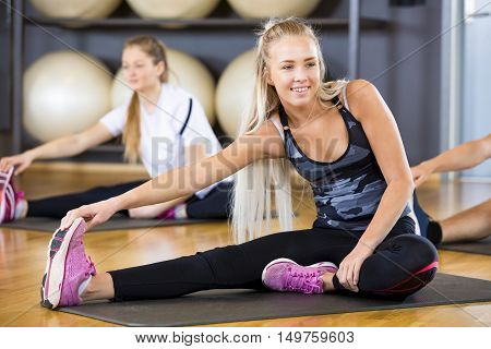 Smiling young woman looking away while streching and holding on toe in gym. Workout team doing stretching excerises for flexibility and balance at the fitness gym.