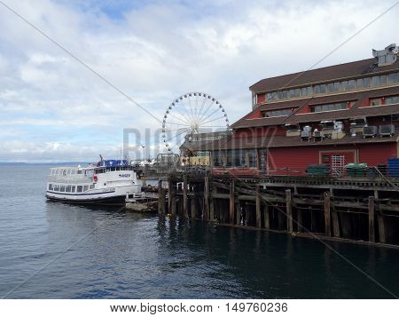 SEATTLE - JUNE 24 2016: Argosy Boat parked at the Docks of the Pier District in Seattle Washington with the Great Wheel in the Distance in Seattle during the summer on June 24 2016.
