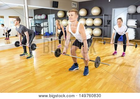 Full length of young male and female friends exercising deadlift with barbells in gym