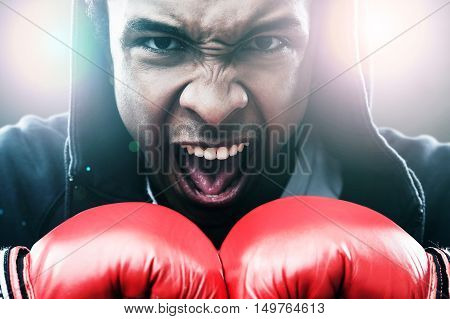 Close up of enraged African American man in boxing gloves. Concept of championship