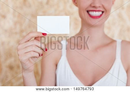 Smiling girl holding a blank business card in her hand with red nails. Concept of advertising an PR. Mock up
