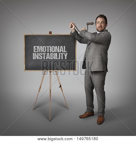 Emotional instability text on blackboard with businessman drilling his head