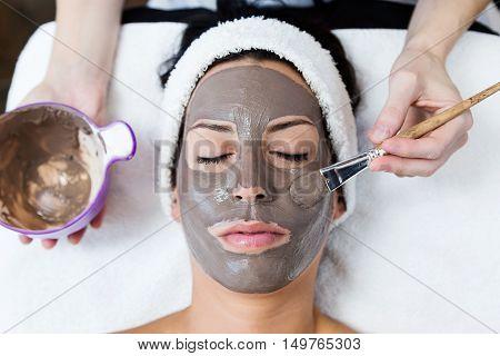 Beautiful Young Woman With Clay Facial Mask In Beauty Spa. Detox Ritual.