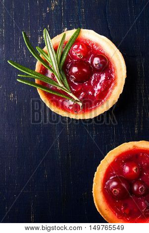 Winter one bite-sized snack or dessert: tartlets with sweet and sour cranberry sauce, decorated with rosemary. Top view, copy space
