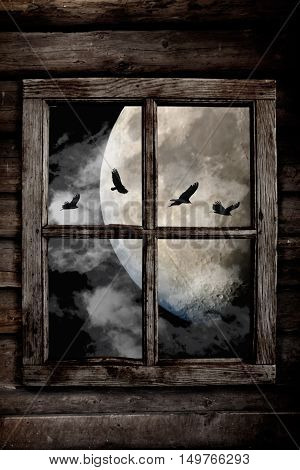 Halloween night ravens flying in front the moon and clouds view through an old wooden cabin window