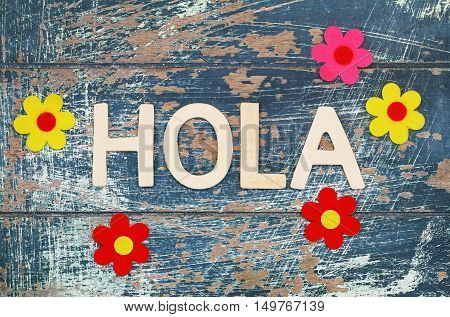 Hola (Hello in Spanish) written with wooden letters on rustic surface and colorful flowers