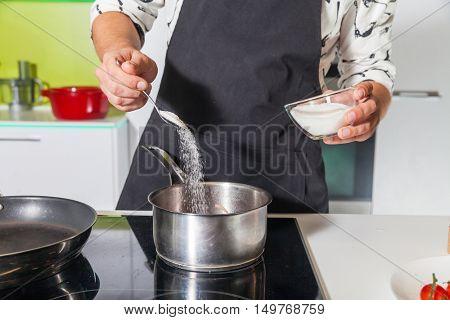 Man sifting sugar in the pan