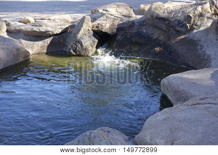 Green waterflowing from decorative boulders and rocks Cortez lake small recreational park in North West Phoenix AZ