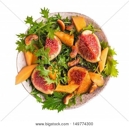 Fresh fig and melon salad with mizuna and smoky cashews isolated on white top view