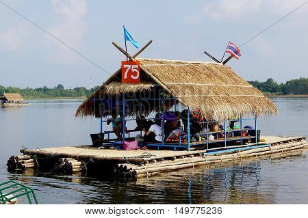 People which is not known is sitting in the platform in the lake.
