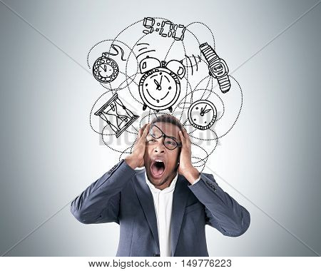 Portrait of frustrated African American businessman crying near gray wall with clock and watch sketches. Concept of time management.