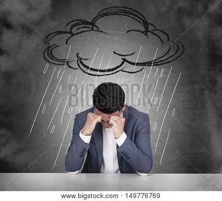 Stressed out Asian businessman sitting under cartoon rain cloud in his office. Concept of bad mood.