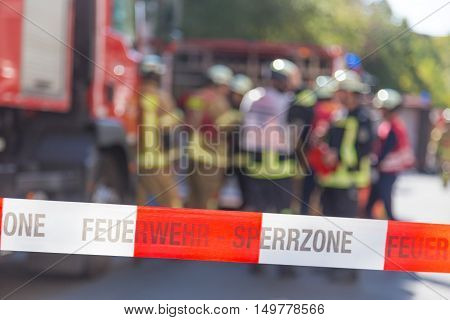 Team of blured firefighters by firetruck on protected accident site. Focus on red and white security band.
