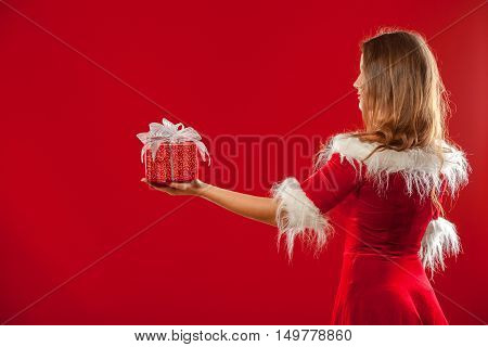 christmas, x-mas, winter, happiness concept - smiling woman in santa helper hat with gift box, over red background