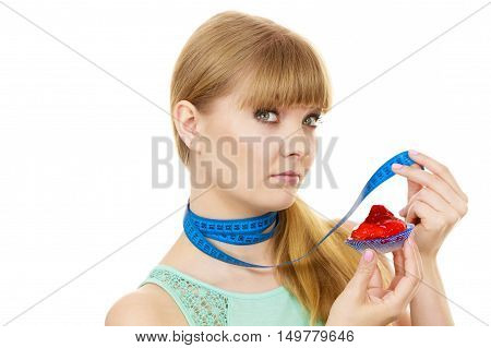 Woman undecided with blue measuring tape around her neck holds in hand cake cupcake trying to resist temptation. Weight loss diet dilemma gluttony concept.