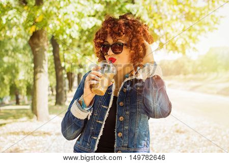 Cool young woman with curly red hair in denim jacket in park in autumn drinking coffee. Happy teenage girl in modern fall outfit drinking takeaway cappuccino, wearing sunglasses, posing.