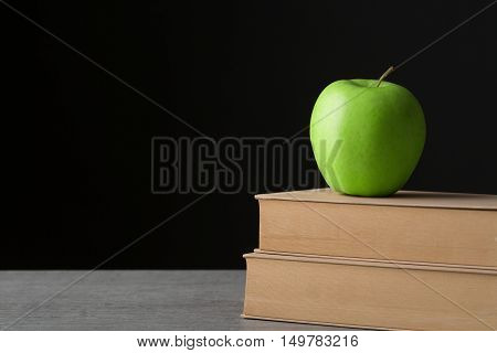 Green apple on the old book with black background
