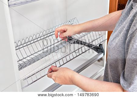 Assembling wall mounted shelf under kitchen cupboard with inside plate rack with drip tray close-up of a woman hands holds wire dish rack.