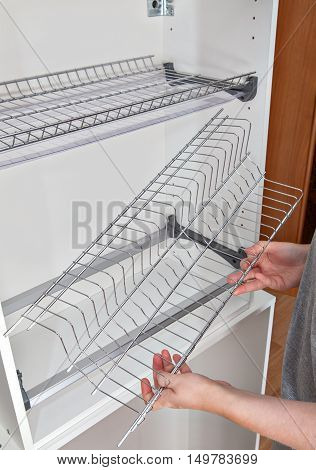 Install wall mounted shelf under kitchen cabinet with inside dish rack with drip tray close-up of a woman hands holds wire part.