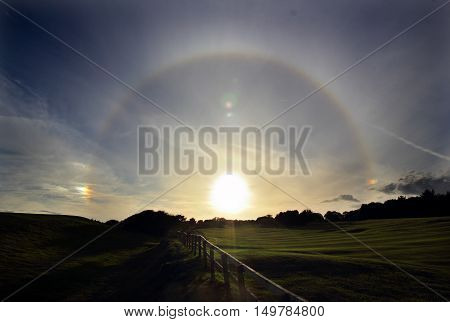 22° degree halo with sun-dogs taken near Alnmouth in Northumberland. These form when light is refracted by hexagonal ice crystals in the atmosphere.