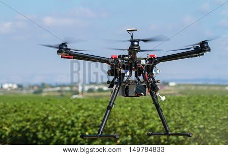 Drone Hovering Over Green Field