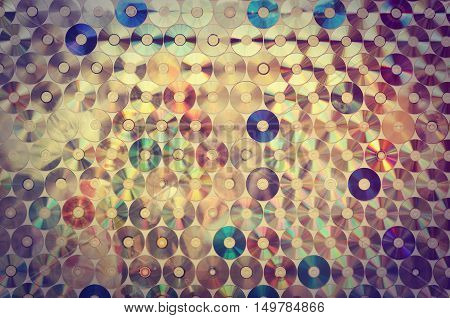 Background on the wall with old damaged discs cd in vintage style.