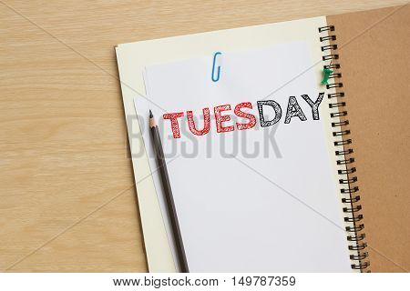 Tuesday text on white paper and pencil, book on wood desk / tuesday concept / top view
