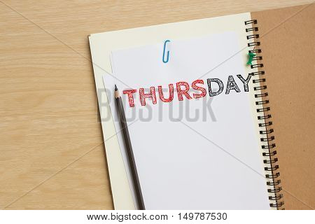 Thursday text on white paper and pencil, book on wood desk / tuesday concept / top view