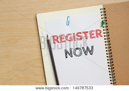 Text Register now on white paper and pencil on the desk / top view / business concept