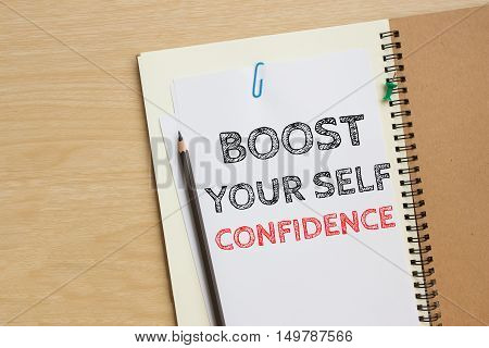 Text boost your self confidence on white paper and pencil on the desk / top view / business concept