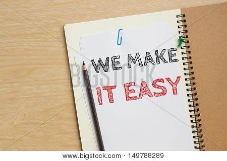 Text we make it easy on white paper with pencil on the desk / business concept