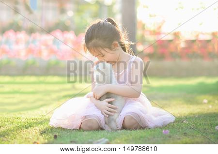 Beautiful asian girl phugging siberian husky puppy in the parkvintage filter