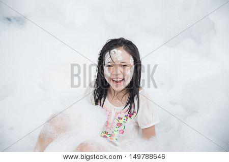 Little asian girl smiling in foam party
