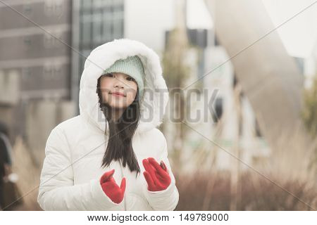 Asian girl enjoying snow in a snowy day in the street of a town