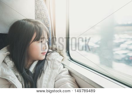 Little asian girl looking through window. She travels on a trainvintage filter