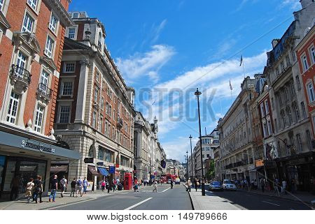 London, United Kingdom - July 7, 2014. View of Piccadilly street in London, with historic buildings, commercial properties, street traffic and people.