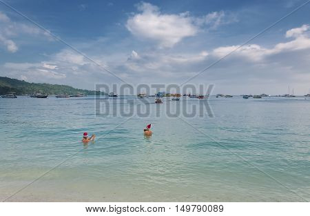 December 25, 2014.  PhiPhi Don Island, Thailand.  Two women wearing santa hats taking pictures on Christmas day on Phiphi don island in Thailand.