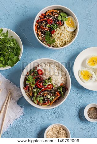 Vegetarian lunch table in the asian style - rice noodles vegetable stir fry boiled eggs. On a blue background top view