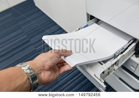 Human hand isteloading paper to printer tray