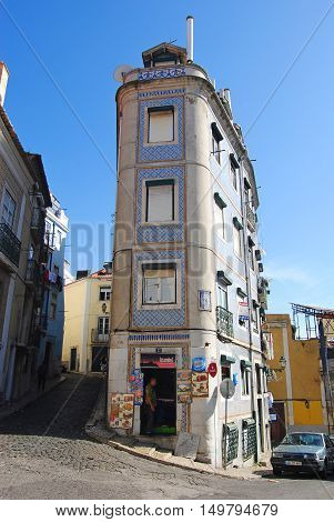 Lisbon, Portugal - October 19, 2014. View of rua de Santa Marinha street in Lisbon, with residential building, commercial properties, cars and people.