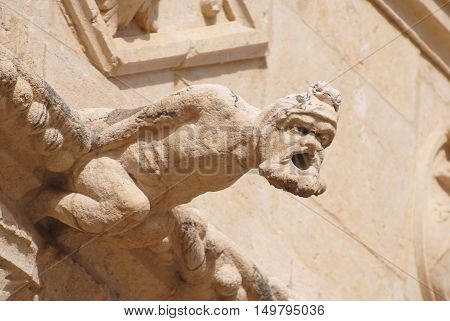 Lisbon, Portugal - October 21, 2014. Gargoyle representing a human figure at the upper balustrade of Mosteiro dos Jeronimos in Lisbon.