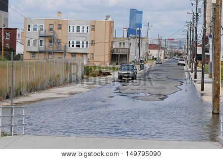 Atlantic City, New Jersey, United States of America - September 7, 2014. American contrasts. Backstreet of a multimillion casino in Atlantic City, with large puddle, cars, buildings and Harrahs Atlantic City resort in the distance.
