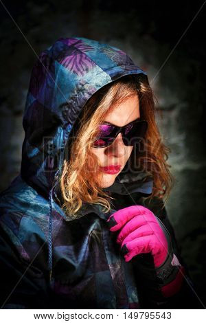 girl with sport glasses and snowboard gear in darkness
