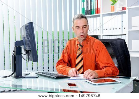 Business Man At His Desk Looking Stressed