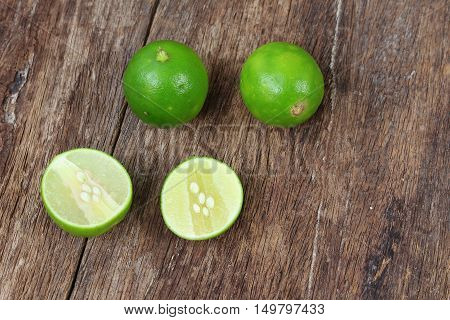 whole and sliced lime on wooden table top view
