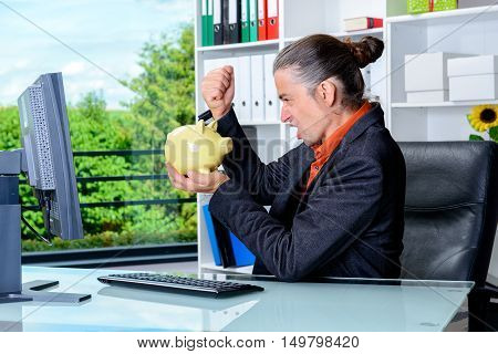Angry Business Man At His Desk With Piggy Bank